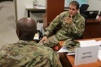 2nd Lt. Daniel Perez, a military intelligence officer assigned to the Headquarters Company, 50th Regional Support Group (RSG), discusses assignments to subordinate units with Staff Sgt. Nakia McCallum at the 50th RSG's Emergency Operations Center in Homestead during the Florida National Guard's annual hurricane readiness exercise. This was Perez' first hurricane exercise since receiving his commission in 2018.