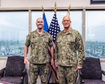 Two military Navy Rear Admirals stand in front of flags