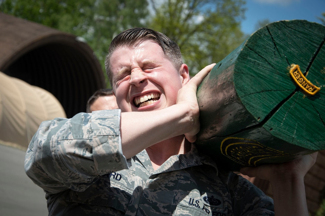 Technical Sgt.  Jason Allard, 48th Communication Squadron noncommissioned officer in charge of quality assurance, rests a log on his shoulder during a team building event.
