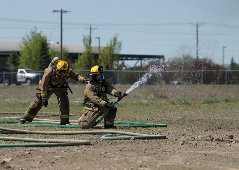 Firefighters from the Airway Heights Fire Department test hose pressure while preparing for a Major Accident Response Exercise drill near Fairchild Air Force Base, Washington, May 9, 2019.