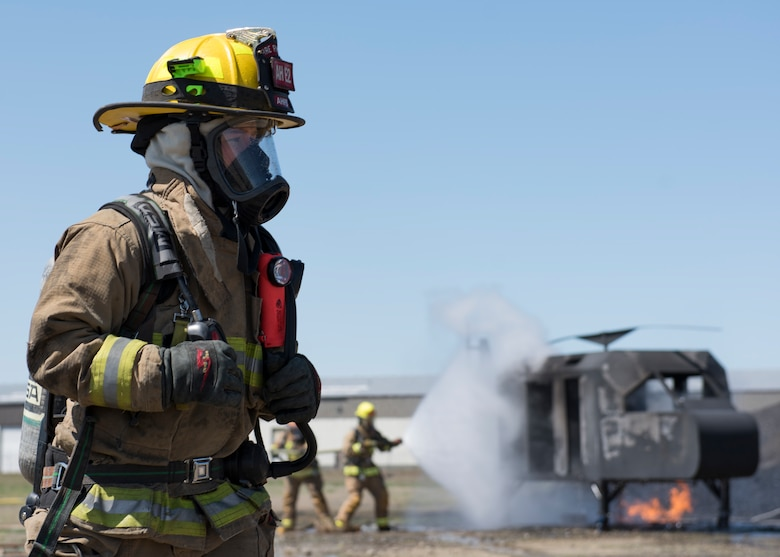 A firefighter from the Airway Heights Fire Department the scene around a helicopter crash trainer during a Major Accident Response Exercise drill near Fairchild Air Force Base, Washington, May 9, 2019.