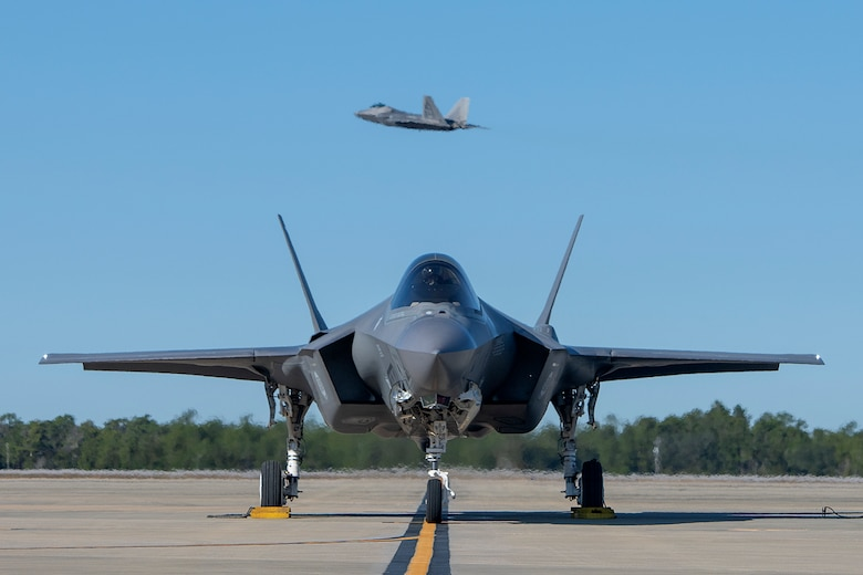 An F-35A Lightning II assigned to the 58th Fighter Squadron awaits permission to taxi as an F-22 Raptor assigned to the 27th Fighter Squadron takes off in the background, Dec. 4, 2018, at Eglin Air Force Base, Fla. (U.S. Air Force Staff Sgt. Peter Thompson)