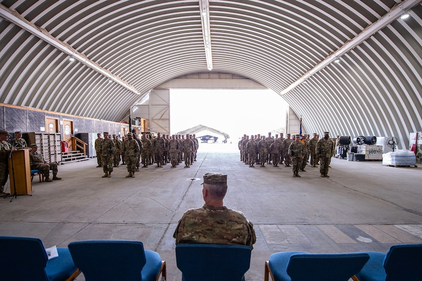 Members of the 35th Combat Aviation Brigade, Missouri Army National Guard, and the 244th Expeditionary Combat Aviation Brigade, U.S. Army Reserve, stand ready during a transfer of authority ceremony in an aircraft hangar in Taji, Iraq, May 1, 2019.  The 35th CAB and 244th ECAB support Combined Joint Task Force – Operation Inherent Resolve and Operation Spartan Shield.  CJTF-OIR works with partner forces to defeat Daesh in designated areas and set conditions for follow-on operations to increase regional stability.