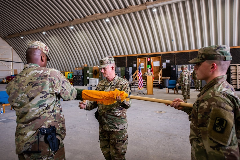 U.S. Army Col. Harvey Cutchin (center), 244th Expeditionary Combat Aviation Brigade, U.S. Army Reserve, and U.S. Army Command Sgt. Maj. Rogelio James, Jr., 244th ECAB (left), unfurl their unit flag during a transfer of authority ceremony in an aircraft hangar in Taji, Iraq, May 1, 2019.  The 244th ECAB supports Combined Joint Task Force – Operation Inherent Resolve and Operation Spartan Shield.  CJTF-OIR works with partner forces to defeat Daesh in designated areas and set conditions for follow-on operations to increase regional stability.