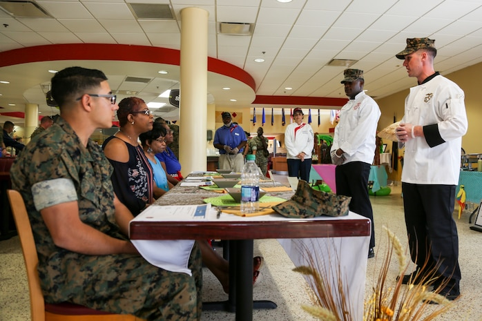 """Sgt. Stephen J. Van Hout, a Quality Assurance Evaluator with the Parris Island Mess Halls aboard Marine Corps Recruit Depot, South Carolina, presents a prepared meal for a panel of judges at Mess Hall 280 on Marine Corps Air Station Beaufort, S.C., May 2, 2019.  The food was prepared during a """"Chef of the Quarter"""" event that includes mess halls from MCAS Beaufort and Parris Island competing against one another for the top spot. Parris Island Mess Hall placed first and won the People's Choice award. (U.S. Marine Corps photo by Cpl. Andrew Neumann)"""