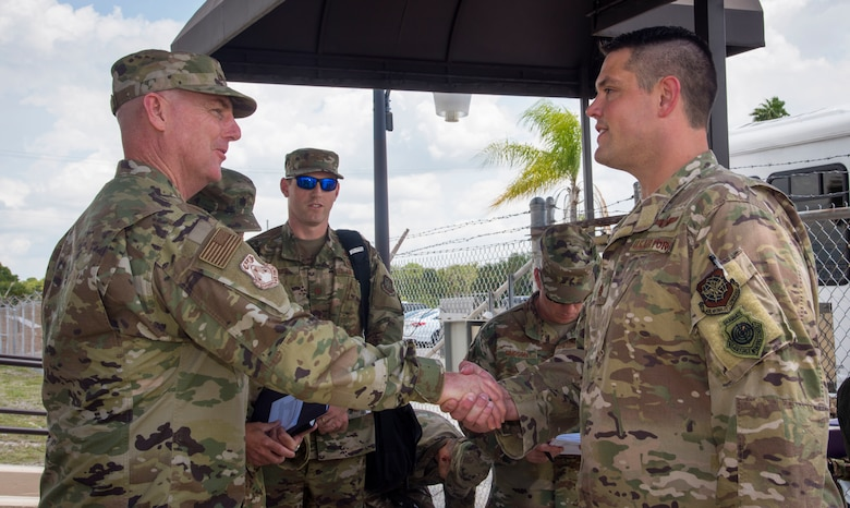 U.S. Air Force Maj. Gen. Sam Barrett, the 18th Air Force commander from Scott Air Force Base, Ill., coins Maj. Benjamin Hedges, the 6th Operations Support Squadron combat support flight commander, at MacDill AFB, Fla., May 9, 2019.