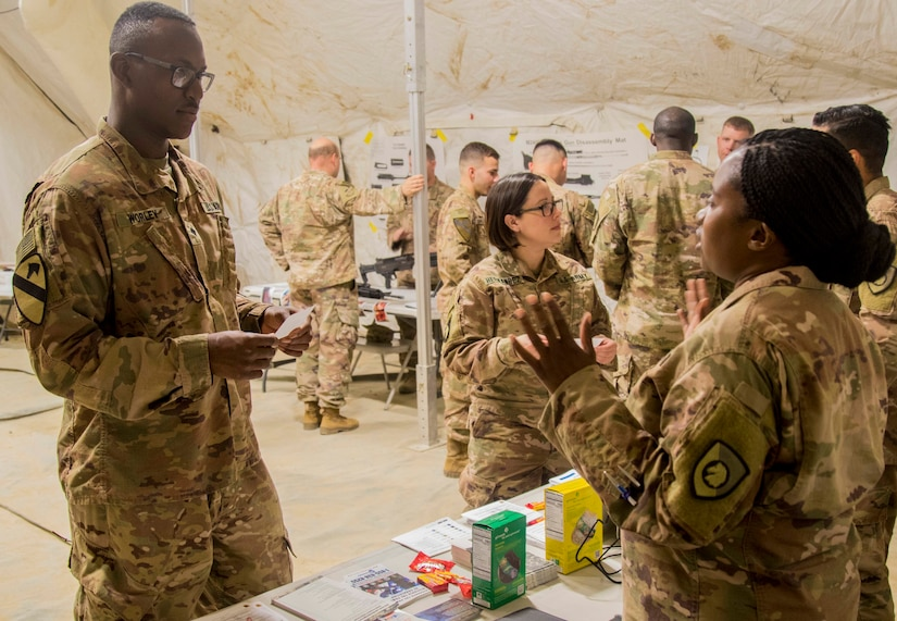 Army Spc. Kadeem Worley, left, assigned to the 502nd Human Resources Company, 4th Special Troops Battalion, 4th Sustainment Brigade, receives information on behavioral health from Capt. Tiffany Taylor, a behavioral health officer assigned to the 300th Special Troops Battalion, 300th Sustainment Brigade, 4th Expeditionary Sustainment Command, at the safety rodeo hosted by the Headquarters and Headquarters Company, 300th STB on Camp Arifjan, Kuwait, May 7, 2019. This event serves to educate Soldiers on how to minimize and prevent accidents or injuries and to increase safety awareness.