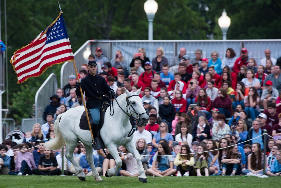 A soldier wearing a vintage uniform and cover holds a flag while riding a white horse in front of a crowd.