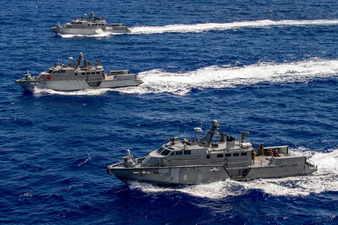 Three ships travel through ocean waters.