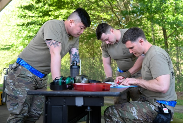 Master Sgt. Tae Choe (left), a ramp services supervisor, Master Sgt. Zach Dunkin (right), NCO in charge of load planning, and Tech. Sgt. Michael Nippers Jr. (right), all assigned to the 76th Aerial Port Squadron, tie down cargo for the pallet build-up event at the Port Dawg Challenge April 24, 2019.