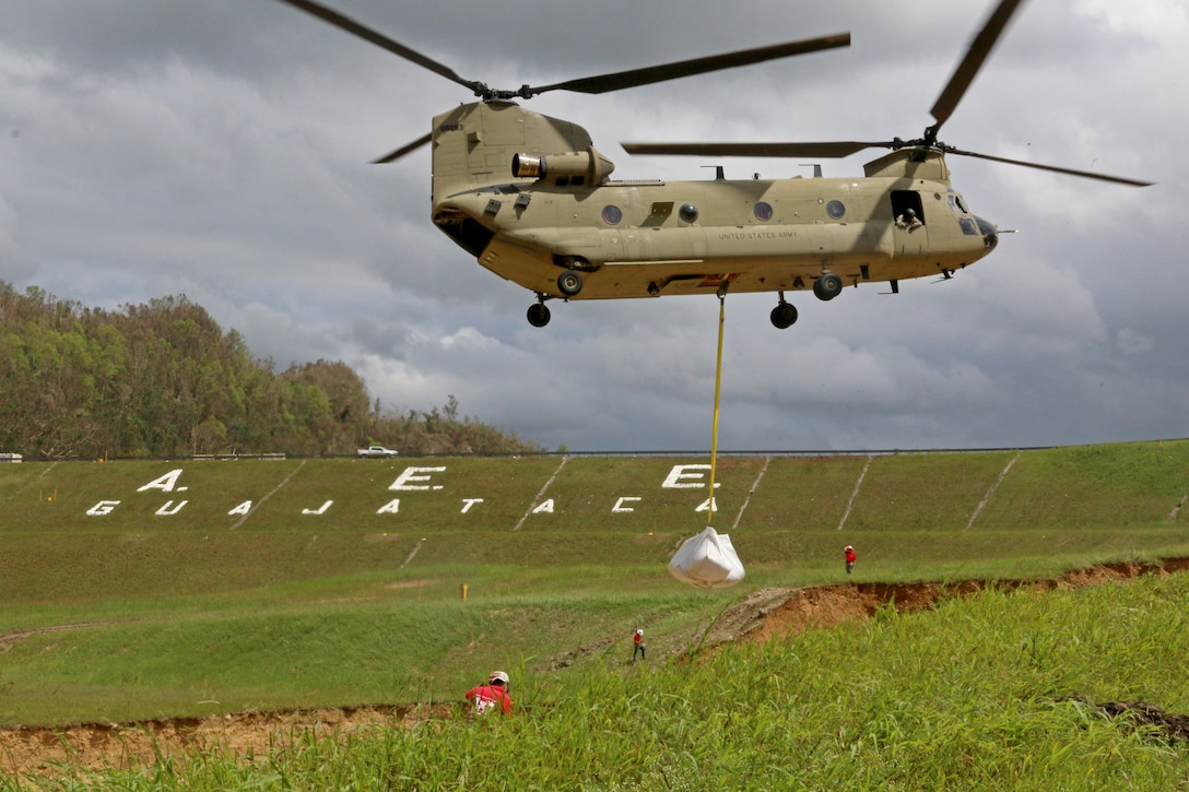 Chinook helicopter places a large sand bag on the spillway