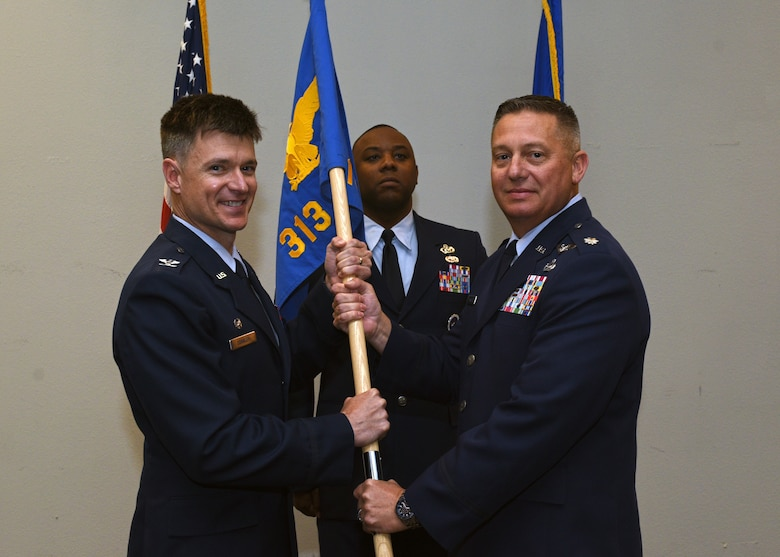 U.S. Air Force Col. Thomas Coakley, 17th Training Group commander, passes the 313th Training Squadron guidon to Lt. Col. Herbert Millet III during a change-of-command ceremony at the event center on Goodfellow Air Force Base, Texas, May 10, 2019. Millet assumed command of the 313th Training Squadron from Lt. Col. David Sarabia during the change of command ceremony. (U.S. Air Force photo by Airman 1st Class Robyn Hunsinger/released)