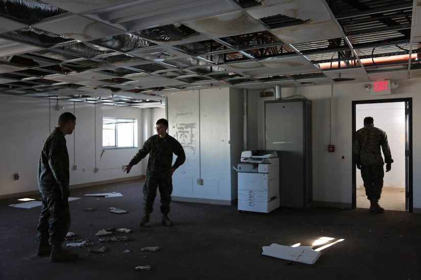 Marines survey storm damage in a building
