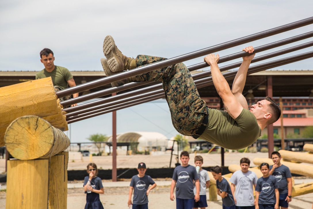 A Marine slides down a pole upside down while a group of young children watch.