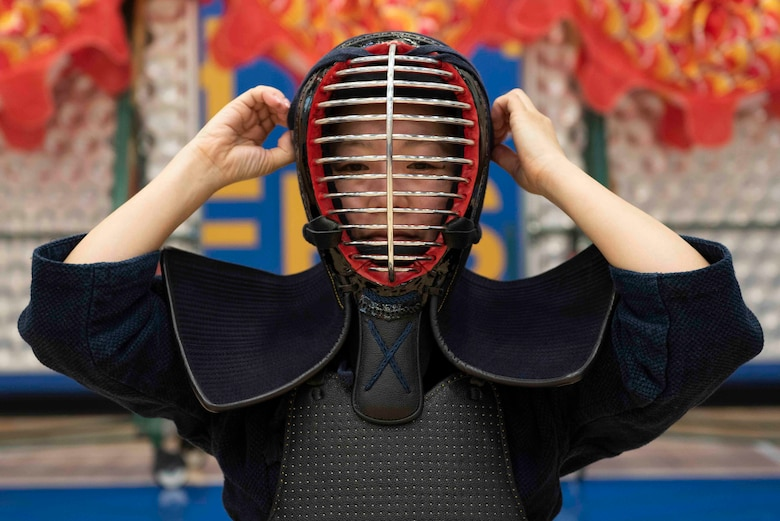 A volunteer secures their mask prior to a Kendo demonstration during the National Asian American and Pacific Islander Heritage Celebration at Yokota High School, Yokota Air Base, Japan, May 6, 2019.