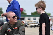 Capt. Kyle, 17th Attack Squadron MQ-9 Reaper pilot, talks with an air show attendee during the Joint Base Andrews 2019 Air and Space Expo on Joint Base Andrews, Maryland, May 10, 2019. The MQ-9 was a static display at this year's show celebrating legends in flight. (U.S. Air Force photo by Airman 1st Class Haley Stevens)