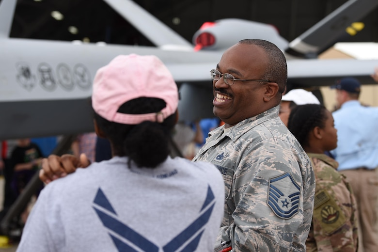 Master Sgt. Barrett, 432nd Maintenance Squadron superintendent, laughs with an attendee during the Joint Base Andrews 2019 Air and Space Expo at Joint Base Andrews, Maryland, May 11, 2019. The MQ-9 Reaper was a static display at this year's show celebrating legends in flight. (U.S. Air Force photo by Airman 1st Class Haley Stevens)