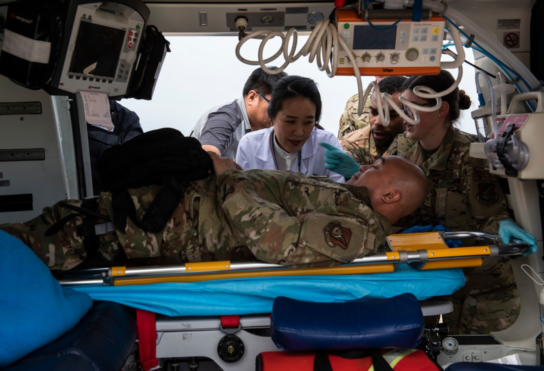 Airmen from the 8th Medical Group and medical staff from Wonkwang University Medical Center load a simulated patient on a helicopter at Kunsan Air Base, Republic of Korea, May 8, 2019. 8th MDG worked closely with the staff at Wonkwang to test how the facility could accommodate an air lift emergency from Kunsan. (U.S. Air Force photo by Senior Airman Stefan Alvarez)
