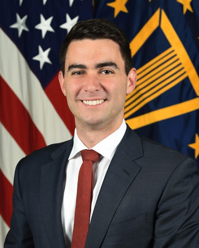 A portrait photo of Matthew Daniels standing in front of the U.S. flag.