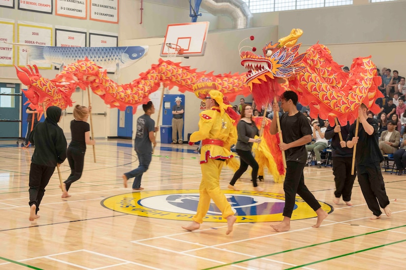 Students hold up a Chinese dragon while dancing on a gym floor as an audience watches.
