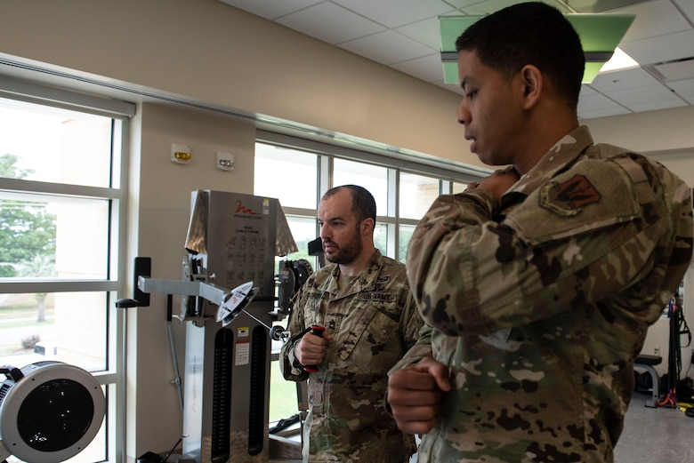 U.S. Army Sgt. 1st Class David Bedford, U.S. Army Central Command explosive ordnance disposal noncommissioned officer, uses a workout machine while U.S. Air Force Staff Sgt. Marcos Davis, 20th Medical Operations Squadron physical therapy technician, demonstrates how to perform the movement at Shaw Air Force Base, S.C., May 10, 2019.