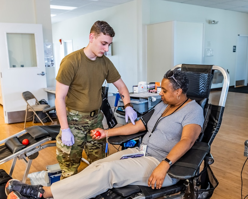 Military man touches vein on sitting woman in preparation of giving blood