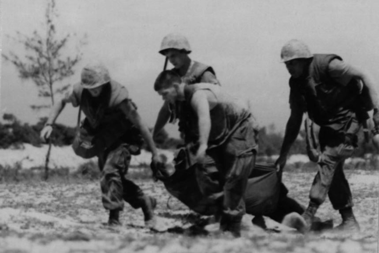Four Marines on a battlefield carry an injured Marine on a makeshift gurney.