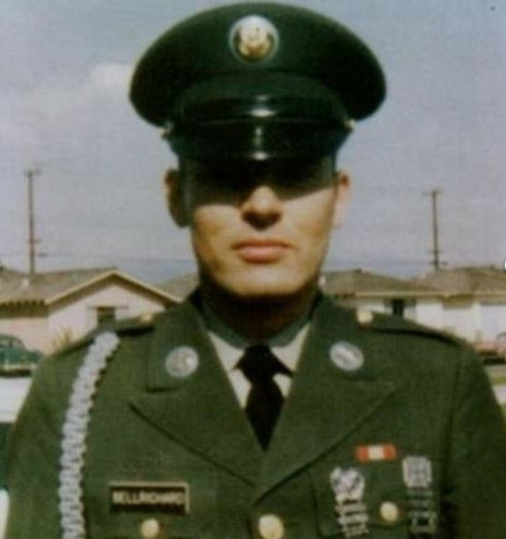 A soldier in dress uniform stands at attention wearing a formal cap.