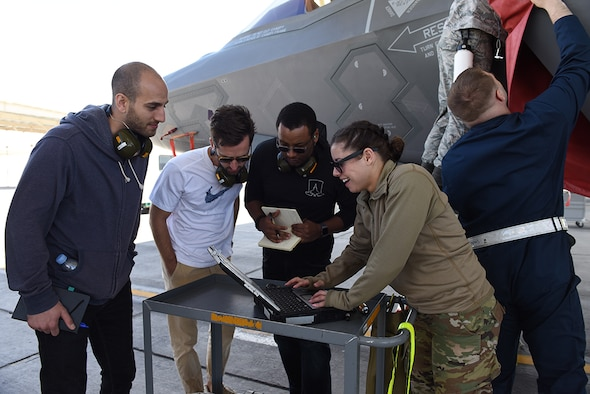 "Ron Golan, Peter Wallace, and DeMarcus Townsend from Detachment 12 at Hanscom Air Force Base, Mass., work with Staff Sgt. Samantha Buxton, dedicated crew chief with the 57th Wing's Bolt Aircraft Maintenance Unit at Nellis Air Force Base, Nev., on the Nellis flightline, near an F-35 Lightning II Joint Strike Fighter April 10, 2019. The ""Mad Hatter"" team from Det. 12 is learning how maintainers navigate technical orders while working on the flightline. (U.S. Air Force photo by Airman 1st Class Bailee Darbaise)"