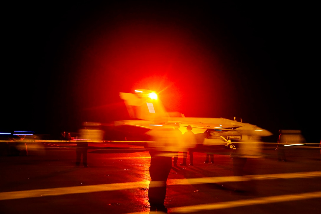 A military jet takes off from an aircraft carrier at night with a red light shining behind it.