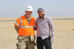 U.S. Army Chief Warrant Officer 3 David Hardigree, 184th Sustainment Command safety officer, stands with a Kuwait work party member during a traffic safety sign setup initiative conducted along routes in the vicinity of Camp Buehring, Kuwait, May 11, 2019.