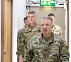Col. Douglas Ottenberg, director of 398th Financial Management Support Center leads Maj. Gen. Bradley Dreyer,  deputy chief of staff, G8, during a visit at Camp Arifjan, Kuwait, Mar. 16, 2019.