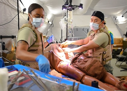 Players in the Expeditionary Medical Support exercise operate on a mannequin, May 9, 2019 at Joint Base Langley-Eustis, Virginia.