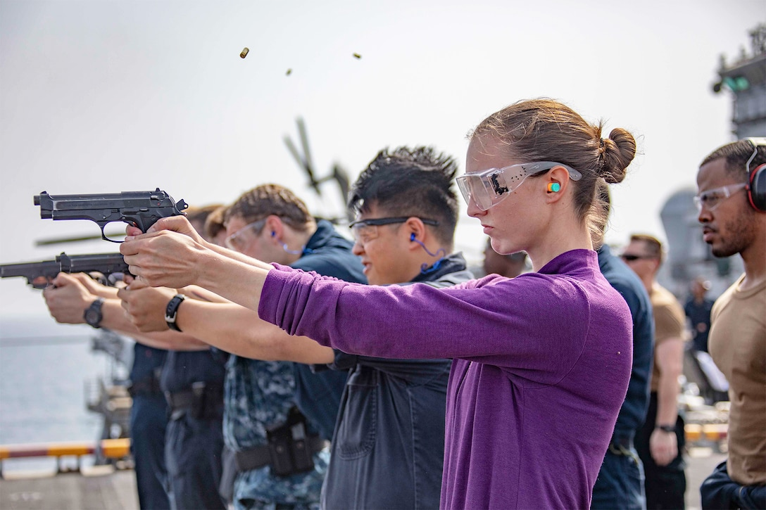 Sailors stand in a row and fire pistols on the flight deck of an assault ship.