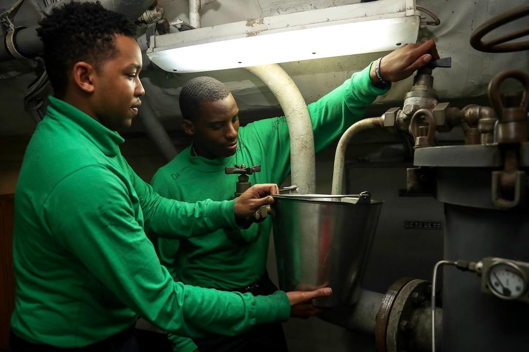 Two Seamen vent a  hydraulic filter below deck.