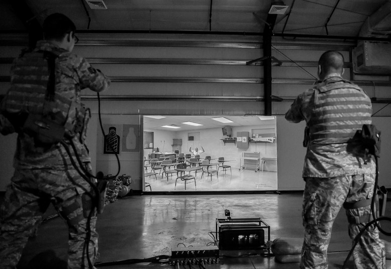 During simulated training at Joint Base Lewis-McChord, Wash., U.S. Air Force Staff Sgt. Chad Rogers, 627th Security Forces Squadron (SFS) noncommissioned officer in charge of plans and programs, and U.S. Air Force Staff Sgt. Kenneth Daugherty, 627th SFS base defense operations controller, orders an active shooter to get on his knees, April 30, 2019. Increased training, equipment upgrades and more were implemented across the 627th SFS as a part of the Reconstitute Defender Initiative to revitalize security forces squadrons across the Air Force. (U.S. Air Force photo by Senior Airman Tryphena Mayhugh)