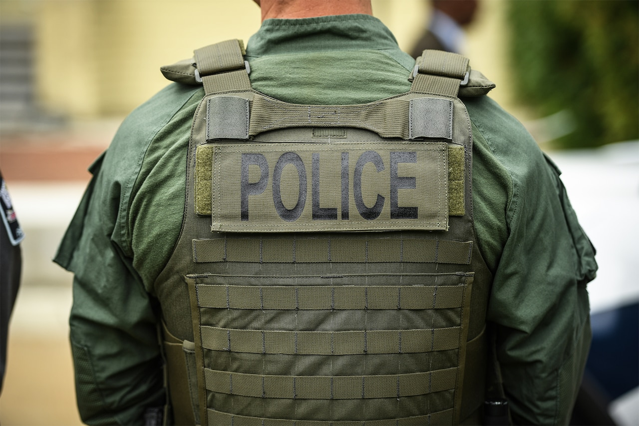 "The back of a police officer's tactical vest bears the word ""police."""