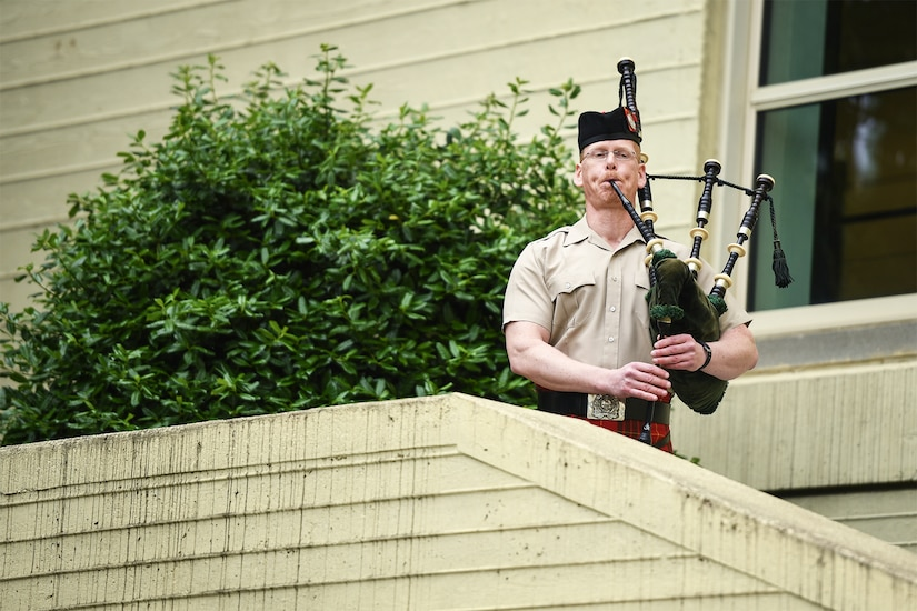 A musician plays bagpipes at the top of a set of stairs.