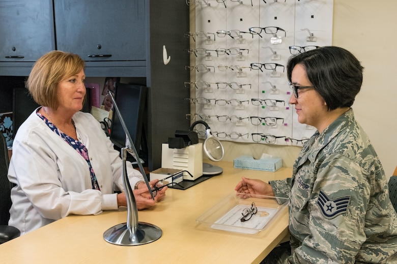 Jennifer Freeman, 436th Aerospace Medicine Squadron ophthalmic technician, watches Staff Sgt. Courtney Herrera, 436th Medical Support Squadron radiologic technologist, try on eye glass frames May 8, 2019, at the Optometry Clinic on Dover Air Force Base, Del. When glasses are needed, picking out and ordering frames is one of the last steps during a routine eye examination. (U.S. Air Force photo by Roland Balik)