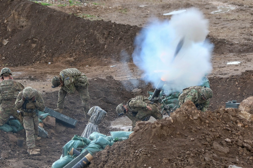 Soldiers fire mortars in the dirt.