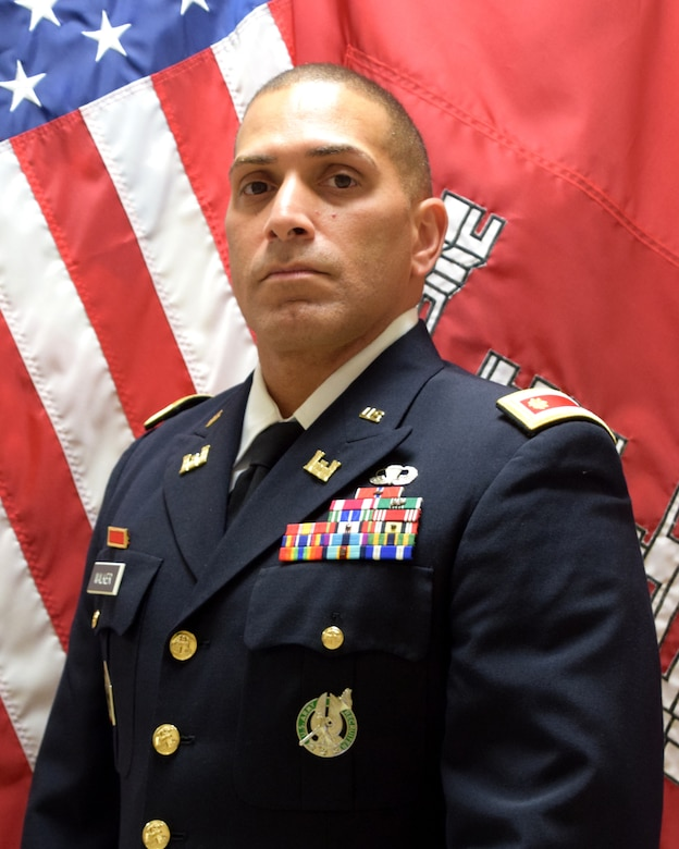 Maj. Alexander Walker wearing Army Service Uniform in front of USA and USACE flags.