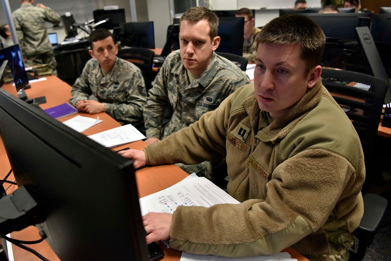 Service members work at a computer.