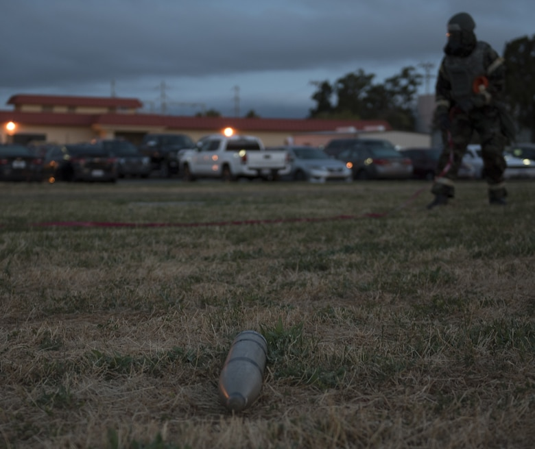 U.S. Air Force Airman 1st Class Kelvin Powell, 60th Medical Group bioenvironmental specialist, sets up a cordon around a fake projectile, May 7, 2019, during a readiness exercise at Travis Air Force Base, California. The base conducted a week-long exercise to evaluate Travis' ability to execute and sustain rapid global mobility operations. (U.S. Air Force photo by Staff Sgt. Amber Carter)