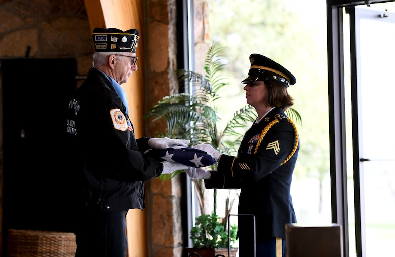 A South Dakota Army National Guardsman hands a folded burial flag over to a member of the Sturgis Honor Guard before it is presented to the family of former Pfc. Carroll E. Lonas at the Black Hills National Cemetery in Sturgis, S.D., May 9, 2019. Lonas was captured by the Germans during World War II and was detained for 14 months prior to his escape. He hiked roughly 1,100 miles until he reached friendly territory. (U.S.  Air Force photo by Airman 1st Class Christina Bennett)