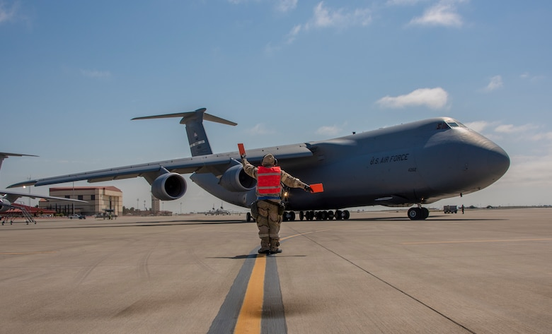 U.S. Air Force Staff Sgt. Corey Fugate, 349th Aircraft Maintenance Squadron marshals a C-5M Super Galaxy during a readiness exercise at Travis Air Force Base, California, May 9, 2019. The base conducted a week-long exercise that evaluated Travis' readiness and ability to execute and sustain rapid global mobility around the world. (U.S. Air Force photo by Heide Couch)