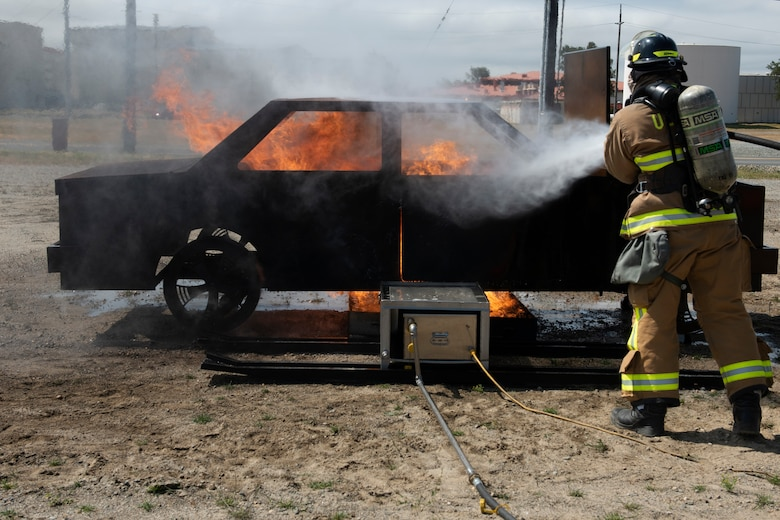 A Firefighter assigned to the 60th Civil Engineer Squadron works to extinguish a fire May 9, 2019 during a training exercise at Travis Air Force Base, California. The base conducted a weeklong exercise to evaluate its ability to execute and sustain rapid global mobility operations. (U.S. Air Force photo by Tech. Sgt. James Hodgman)