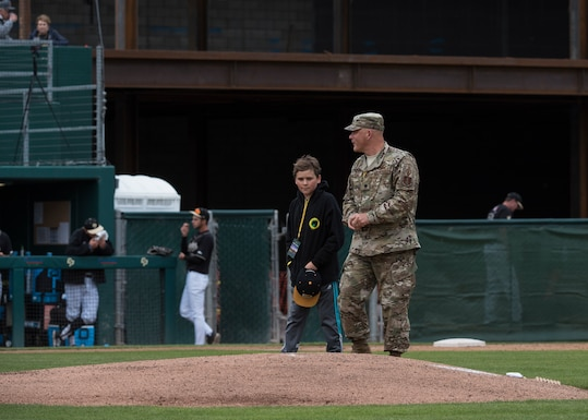 """Lt. Col. Steven Kimel, 216th Space Control Squadron commander, approaches the pitcher's mound with his son to throw the first pitch during the California Polytechnic State University Hero's Night baseball game May 7, 2019, at the Alex G. Spanos Stadium in San Luis Obispo, Calif. The game was dedicated as """"Hero's Night"""" to honor all military, law enforcement and fire personnel. (U.S. Air Force photo by Airman 1st Class Aubree Milks)"""