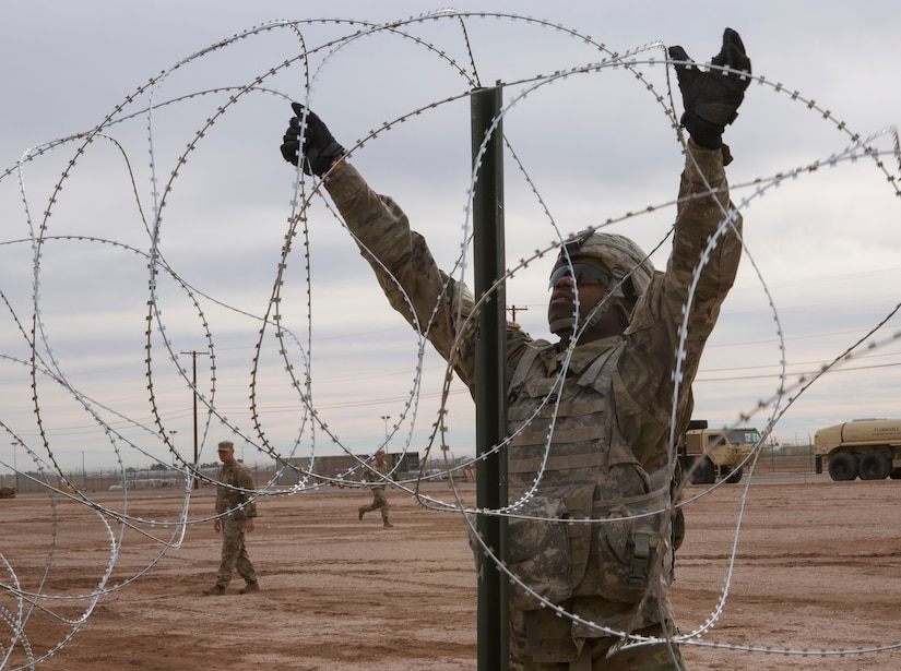 Soldier with 541st Engineer Company, Special Purpose Marine Air-Ground Task Force 7, moves concertina wire over stake on practice barricade at Naval Air Facility El Centro in California, December 4, 2018 (U.S. Marine Corps/Asia J. Sorenson)