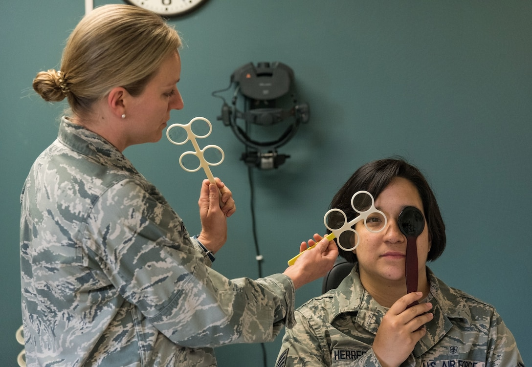U.S. Air Force Maj. Carli Murphy, 436th Aerospace Medicine Squadron optometry flight commander, performs a test on Staff Sgt. Courtney Herrera, 436th Medical Support Squadron radiologic technologist, during a routine eye examination May 8, 2019, at the Optometry Clinic on Dover Air Force Base, Del. The test allowed Murphy to refine Herrera's contact lens prescription. (U.S. Air Force photo by Roland Balik)