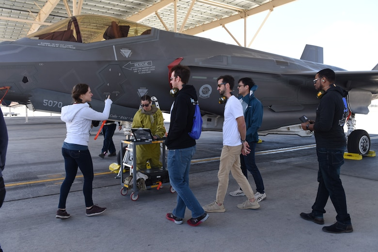 Maj. Jennifer Kannegaard, left, a product manager for the Mad Hatter F-35 Lightning II Joint Strike Fighter software project, leads her software design team to a working area for 57th Wing Bolt Aircraft maintenance unit maintainers April 10, 2019 at Nellis Air Force Base, Nev. Kannegaard's team is working to equip Nellis maintainers with programs that will quickly and easily locate the most up-to-date technical orders for use in aircraft maintenance. (U.S. Air Force photo by Airman 1st Class Bailee Darbaise)